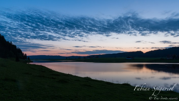Vue du ciel au crépuscule sur les berges du Lac des Taillères dans la Vallée de la Brévine. Le ciel moutonné laissera bientôt place à la voute céleste étoilée.