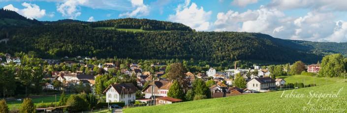 Vue panoramique du village de Couvet (Val-de-Travers), plongé dans un écrin de verdure.