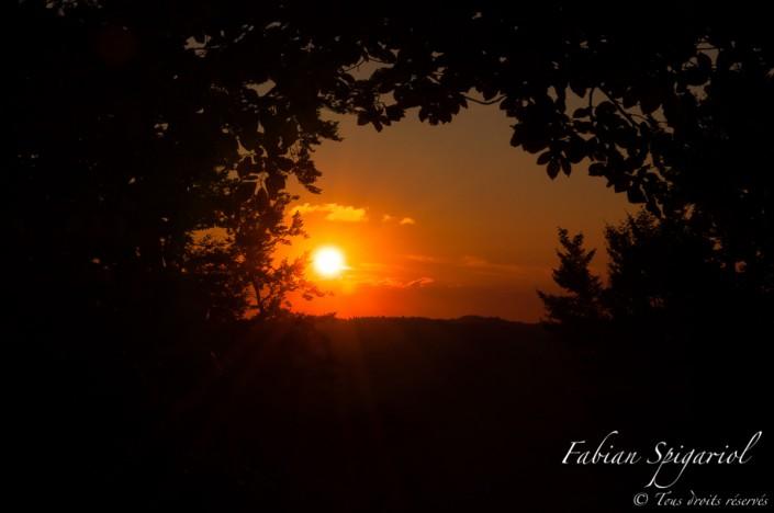 Fenêtre forestière sur un superbe coucher de soleil - C'est dans une trouée forestière des hauteurs du Val-de-Travers que le soleil rougeoyant tire sa révérence.