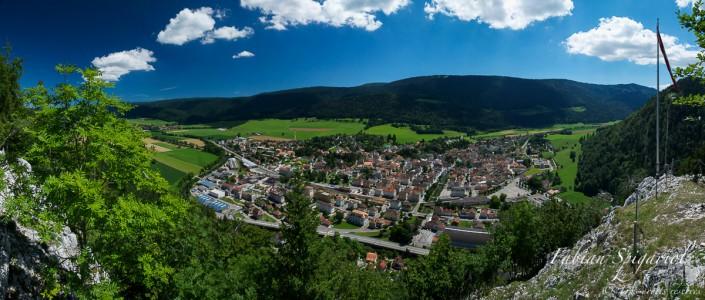 Photographie panoramique et aérienne du village de Fleurier (Val-de-Travers) prise depuis la Caroline un jour d'été.